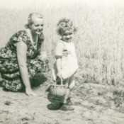 A vintage black and white photo of a woman and a child next to a field.
