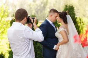 A photographer taking pictures of a couple on their wedding day.