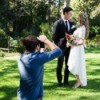 A photographer taking pictures of a wedding couple.