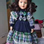 Identifying Porcelain Dolls - dark haired doll wearing a plaid and dark blue dress