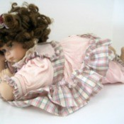 Identifying a Porcelain Doll - doll in pink and plaid outfit lying down