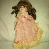 Value of a Brinn Porcelain Doll - dark haired doll wearing a pink lace trimmed outfit