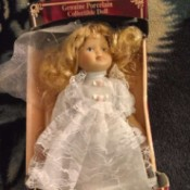 Value of a Porcelain Doll - unidentified doll in a box, wearing a white lace trimmed dress