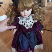 Identifying Porcelain Dolls - doll with ringlets wearing a plum colored dress with white lace trim
