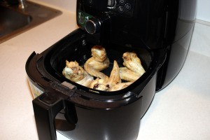 An air fryer with chicken wings inside.