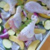 Chicken and vegetables being cooked on a sheet pan.