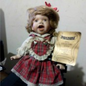 Value of a Seymour Mann Porcelain Doll - doll wearing a red plaid dress holding a certificate