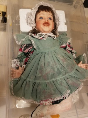 Identifying a Porcelain Doll - doll wearing a patchwork pattern dress with a green pinafore over it
