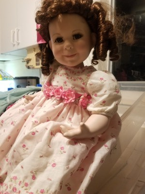 Identifying a Porcelain Doll - doll with ringlets wearing a flowered dress