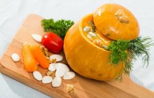 A soup being served inside a baked pumpkin shell.