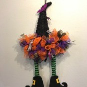 A witch hat decorated with ribbons and striped witch legs, as a Halloween decoration.