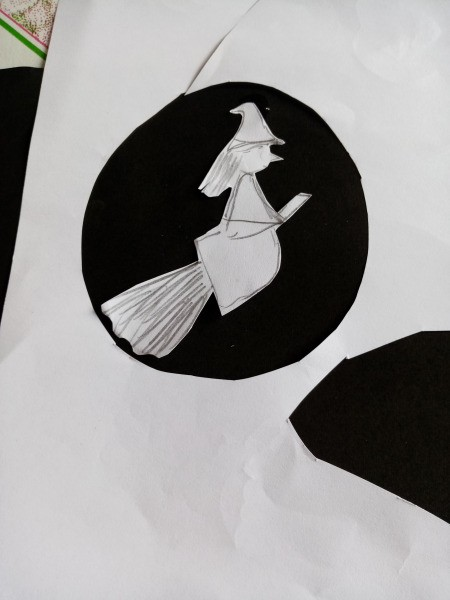 Halloween Toothbrush Spray Painting - hand sketched witch on a broomstick and a circle cut in white paper for the moon