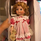 Identifying a Porcelain Doll - doll wearing a red gingham dress with a white pinafore