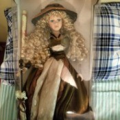 Value of a Collector's Choice Porcelain Doll - blond doll with very long ringlets, wearing a brown and cream dress and holding perhaps a twig broom