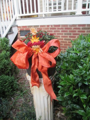 Dressing Up Your Garden With Ribbon - potted mums on white column pedestal decorated with orange ribbon and small figure tuck in bow
