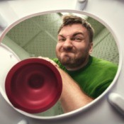A man using a toilet plunger.