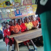 Finding an Agency to Help with Free School Desks in Uganda - children at a long crowded desk
