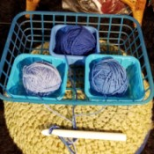 Three balls of yarn that are in different containers to avoid tangling.