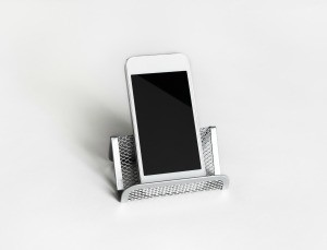 A business card holder being used as a cell phone stand.