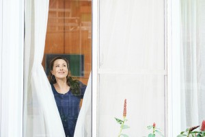 A woman closing curtains in a large window.