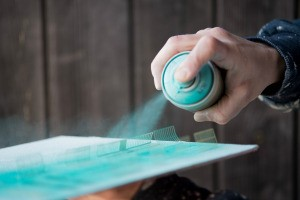 A person using a can of blue-green spray paint.