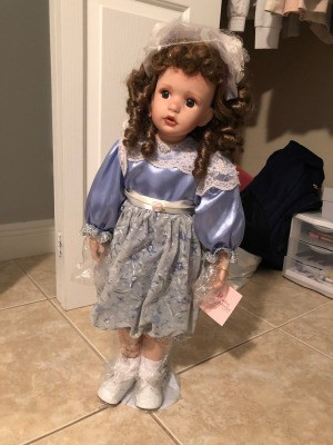 Value of a Paradise Porcelain Doll - doll in stand, wearing a blue satin dress with lace trim
