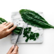 Kale leaves being chopped on a cutting board.