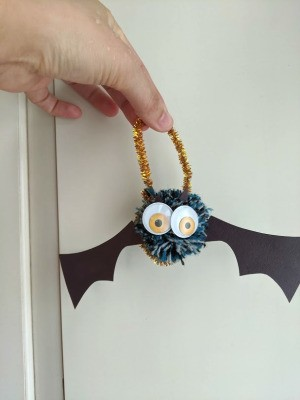 Pom Pom Bat Decoration - hand holding the bat hanging from a gold pipe cleaner