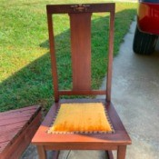 Value of an Old Rocking Chair - armless rocking chair with metal decoration on back and gold upholstered seat