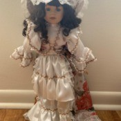 Identifying a Porcelain Doll - doll wearing a long white dress with a floral train and white hat