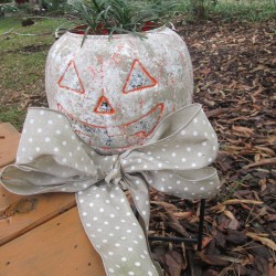 Stone Looking Pumpkin Planters - orange pumpkin outside with bow round the base and plant inside