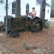 An old tractor being driven by a mannequin.