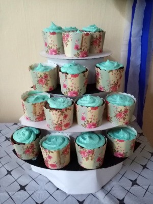 DIY 4 Tier Cupcake Stand - blue frosted cupcakes with floral paper wrappings on the stand for the party