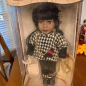 Value of a Collector's Choice Porcelain Doll - doll in box wearing a houndstooth jacket