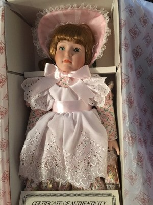 Value of Porcelain Dolls -doll wearing floral dress with matching hat and white eyelet lace apron