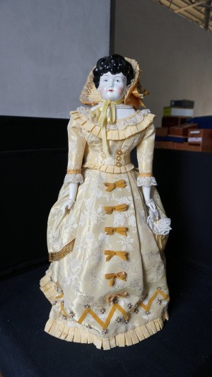 Identifying a Porcelain Doll - very old style porcelain doll in long beige dress with matching bonnet