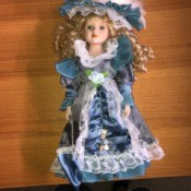 Value of a Cathay Porcelain Doll - doll wearing a blue satin dress and matching hat
