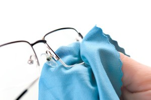 Using a cloth to clean eye glasses