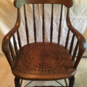 Identifying an Antique Chair - wooden arm chair with perforated wooden seat creating a star pattern and turned legs and rails between the legs