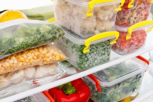 Plastic container full of frozen vegetables.