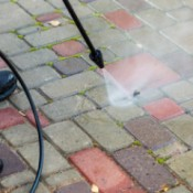 Pressure washing concrete pavers.
