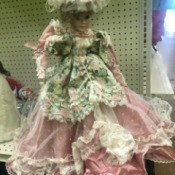 Identifying a Porcelain Doll - doll in fancy pink dress overlain with a  lace layer and a floral overskirt