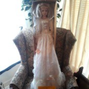 Finding the Value of Ashley Belle Dolls - tall doll wearing a long white dress standing in the box on a chair