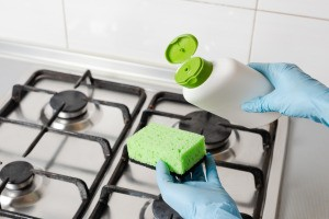 Cleaning gas burners with a sponge.
