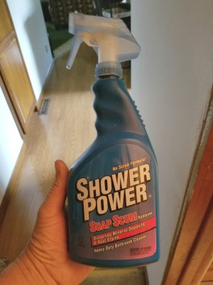 Buying Shower Power Cleaner - hand holding a bottle of Shower Power Cleaner