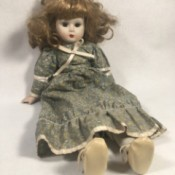 Identifying a Porcelain Doll - doll with mussed up hair wearing a long print dress