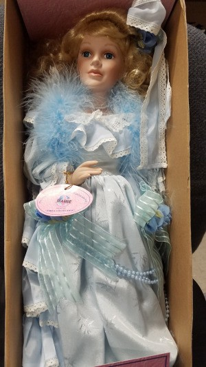 Value of a J. Misa Porcelain Doll - doll in a box wearing a pale blue dress and a feather boa.