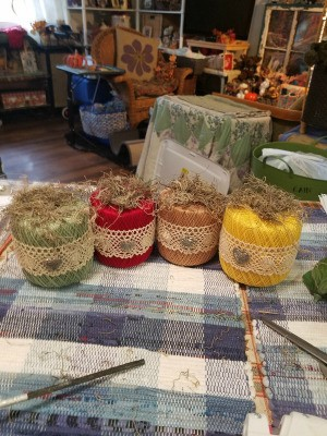 Crochet Thread Spool Pumpkins - the four finished pumpkins sitting on a tablecloth