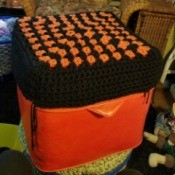 Recovering an Old Hassock - hassock top covered with a large black and orange granny square