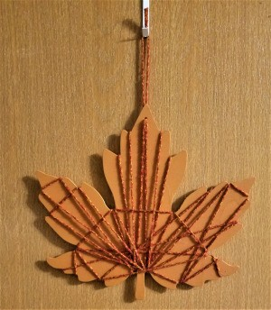 Yarn Embellished Wooden Maple Leaf - finished leaf hanging on the wall